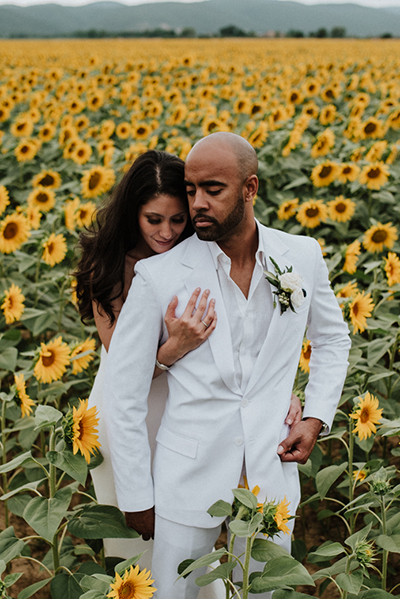 Wedding Couple dressed in white in the middle of a sunflower field